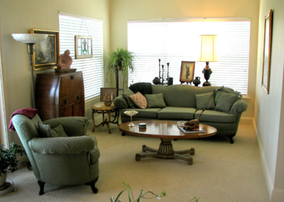 Senior move managers carefully arranged living room furniture in new retirement home.