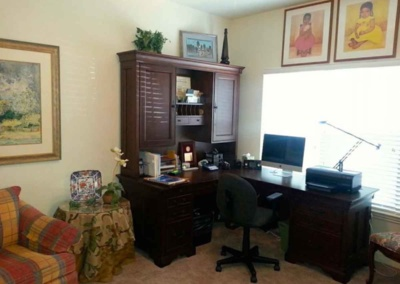 Professional organizers set up office area for older adult during move to retirement facility.
